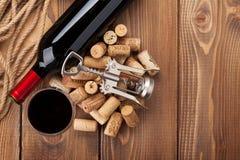 Exponeringsglas av rött vin, flaskan och korkskruvet på den lantliga trätabellen Arkivbild