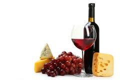 Exponeringsglas av rött vin, ostar och druvor som isoleras på en vit Arkivfoto