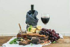 Exponeringsglas av rött vin-, ostbräde-, druva-, fikonträd-, jordgubbe-, honung- och brödpinnar på den lantliga trätabellen, ljus Royaltyfri Fotografi