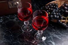 Exponeringsglas av rött vin på mörk marmorbakgrund Klunga av den blåa graen Arkivbild