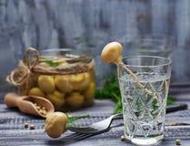 Exponeringsglas av rysk vodka och gravade champinjoner Royaltyfri Bild