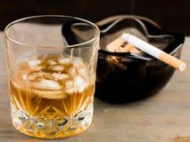 Exponeringsglas av skotsk whisky och en cigarett i ett askfat Royaltyfria Foton