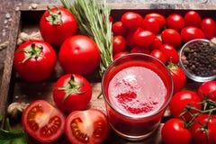 Exponeringsglas av smaklig organisk tomatfruktsaft och nya tomater och örter på trämagasinet i lantlig stil Arkivfoto