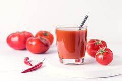Exponeringsglas av smaklig tomatfruktsaft med rå tomater på sund vit träbakgrund bantar Detoxdrinken Royaltyfri Fotografi