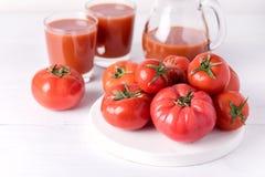 Exponeringsglas av smaklig tomatfruktsaft med rå tomater på sund vit träbakgrund bantar Detoxdrinken Arkivbilder