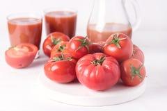 Exponeringsglas av smaklig tomatfruktsaft med rå tomater på sund vit träbakgrund bantar Detoxdrinken Fotografering för Bildbyråer