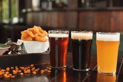 Exponeringsglas av smakligt öl och mellanmål på trätabellen arkivfoton