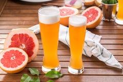 Exponeringsglas av surt grapefrukthantverköl på trätabellen arkivbild
