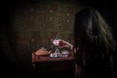 Exponeringsglas av svart te i kvinnas hand på den låga ljusa vardagsrummet som är inre med matta Östligt tebegrepp Östliga mellan royaltyfri bild