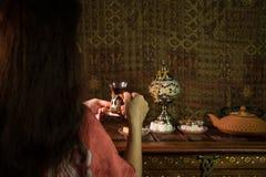 Exponeringsglas av svart te i kvinnas hand på den låga ljusa vardagsrummet som är inre med matta Östligt tebegrepp Östliga mellan fotografering för bildbyråer