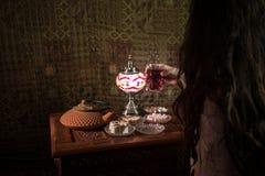 Exponeringsglas av svart te i kvinnas hand på den låga ljusa vardagsrummet som är inre med matta Östligt tebegrepp Östliga mellan royaltyfria bilder