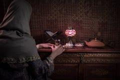 Exponeringsglas av svart te i kvinnas hand på den låga ljusa vardagsrummet som är inre med matta Östligt tebegrepp Östliga mellan arkivfoton