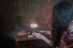 Exponeringsglas av svart te i kvinnas hand på den låga ljusa vardagsrummet som är inre med matta Östligt tebegrepp Östliga mellan royaltyfria foton