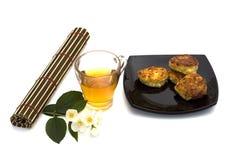 Exponeringsglas av te med ostkakor på en filt Royaltyfri Fotografi