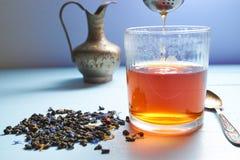 Exponeringsglas av te med tefiltert ut Royaltyfri Bild