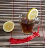 Exponeringsglas av te och den närliggande citronen, på en filt Royaltyfria Bilder