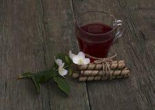 Exponeringsglas av te på en gammal tabell dekorerade med kakor och en blomma Royaltyfri Fotografi