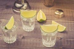 exponeringsglas av tequila med en limefrukt/en förberedelse av skott med en limefrukt på en träbakgrund arkivfoto