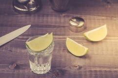 Exponeringsglas av tequila med en limefrukt/en förberedelse av skottet med en limefrukt i en shaker Top besk?dar arkivfoton