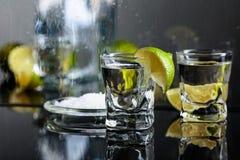 Exponeringsglas av tequila med limefrukt och att salta p? den svarta reflekterande bakgrunden arkivbilder