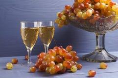 Exponeringsglas av ungt vin med druvor royaltyfri foto