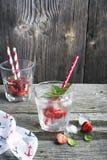 Exponeringsglas av uppfriskande isvatten med saftiga mogna jordgubbar för skivor, mintkaramellsidor och kuber i en enkel träbakgr Arkivfoton