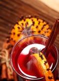 Exponeringsglas av varmt funderat vin för jul på trätabellen med art och apelsiner mot djupfryst fönster closeup Top beskådar arkivfoto