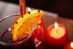 Exponeringsglas av varmt funderat vin för jul på trätabellen med röda stearinljus mot svart bakgrund closeup royaltyfri fotografi