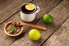 Exponeringsglas av varmt te med limefrukt, citronen, mintkaramellen och farin på den gamla trätabellen Mörk lantlig stil arkivbilder