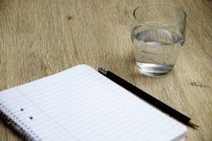 Exponeringsglas av vatten, anteckningsboken och pennan royaltyfri bild