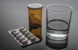 Exponeringsglas av vatten bredvid blåsapacke av piller fotografering för bildbyråer