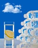 Exponeringsglas av vatten bredvid flaskor av vatten Royaltyfria Foton