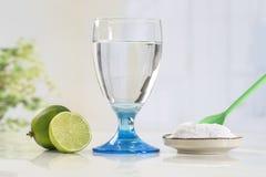 Exponeringsglas av vatten, citron, natureal lösning för sodavattenbikarbonat royaltyfria bilder