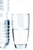 Exponeringsglas av vatten framme av vattenflaskan som isoleras på vit Royaltyfria Foton