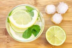 Exponeringsglas av vatten med citronen och mintkaramellen Arkivfoto