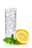 Exponeringsglas av vatten med is, citronen och mintkaramellen royaltyfria foton