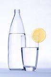 Exponeringsglas av vatten med citronen som är främst av vattenflaskan som isoleras på w Royaltyfri Fotografi