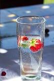 Exponeringsglas av vatten med jordgubbar Royaltyfria Bilder