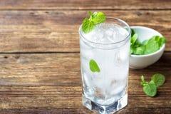 Exponeringsglas av vatten med is och mintkaramellen royaltyfria foton