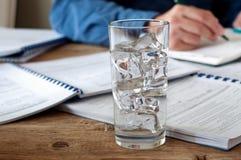 Exponeringsglas av vatten med is på ett teble träkontor Royaltyfri Fotografi