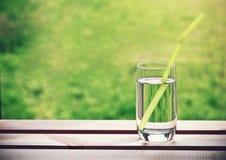 Exponeringsglas av vatten med röret arkivbild