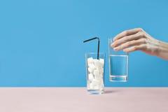 Exponeringsglas av vatten mot socker, sockersjukasjukdomen, söt böjelse, hand tar ett exponeringsglas Fotografering för Bildbyråer