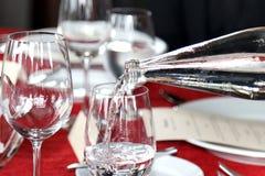 Exponeringsglas av vatten och flaskan häller vatten i exponeringsglas, kallt vatten, vattendrink Arkivbilder