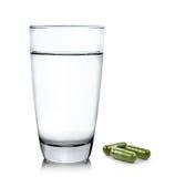 Exponeringsglas av vatten och moringa kapselpreventivpillerar på vit bakgrund royaltyfri fotografi