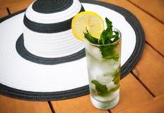 Exponeringsglas av vatten och sommarhatten Selektiv fokus på exponeringsglas Royaltyfria Foton