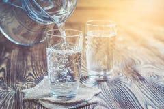 Exponeringsglas av vatten på en trätabell Royaltyfri Fotografi