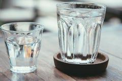 Exponeringsglas av vatten på en trätabell Royaltyfri Bild