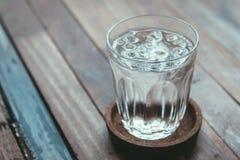 Exponeringsglas av vatten på en trätabell Royaltyfria Foton