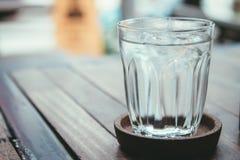 Exponeringsglas av vatten på en trätabell Arkivfoton