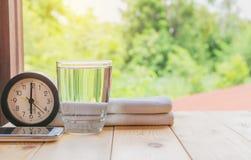 Exponeringsglas av vatten på en trätabell med klockan och näsduken Arkivfoton